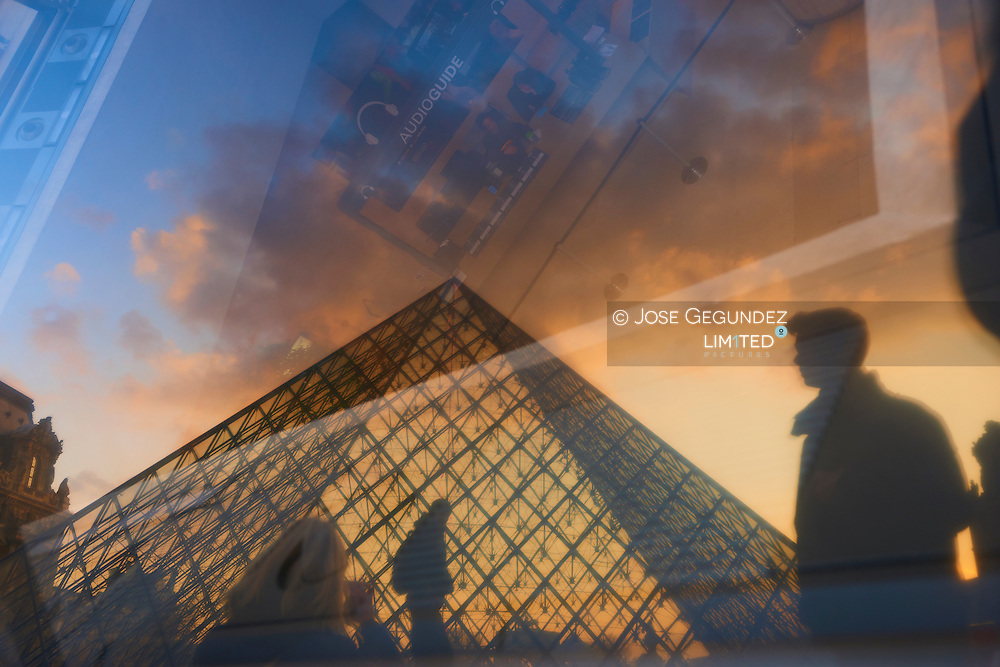 Glass pyramid and Louvre in the evening at sunset, Paris