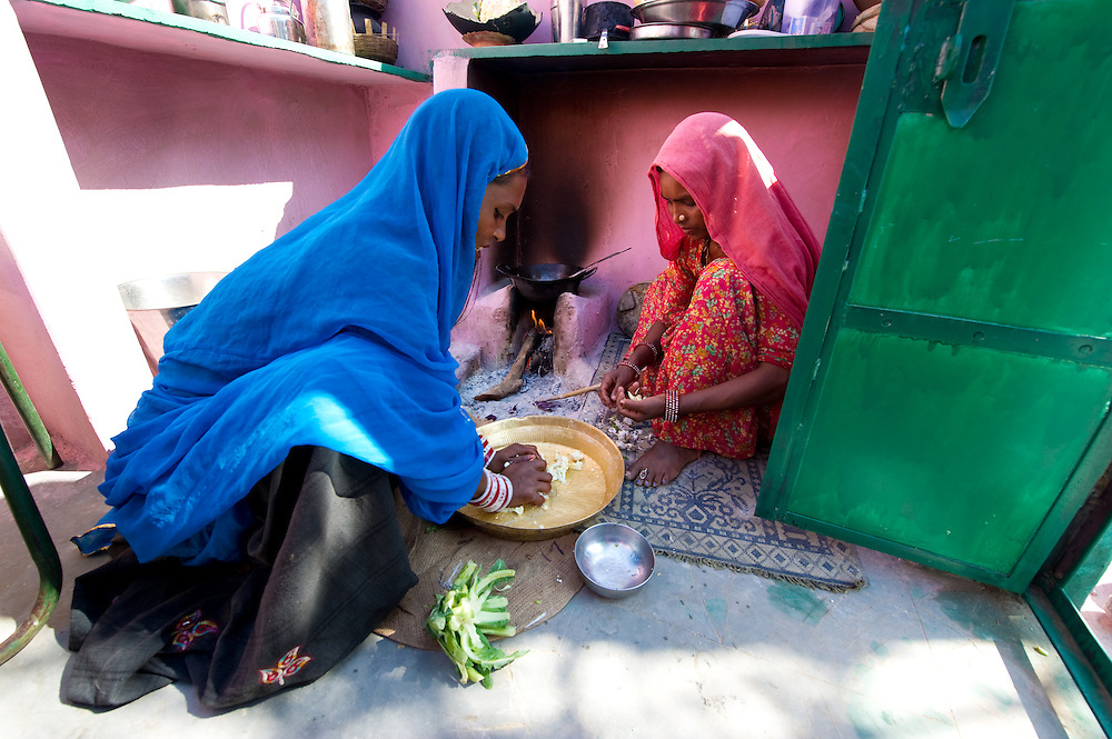 Two sisters from the Bhopa tribe in Rajasthan, preparing a vegetarian meal in a traditional kitchen.