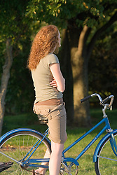 Pretty girl with red hair leaning on her bicycle seat with her arms crossed