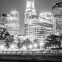 Boston cityscape at night black and white photo along the Boston Harbor waterfront with Custom House Tower clock and downtown Boston buildings.