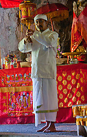 Priest at red altar inside the cave temple complex at Goa Giri Putri on Nusa Penida, Bali, Indonesia