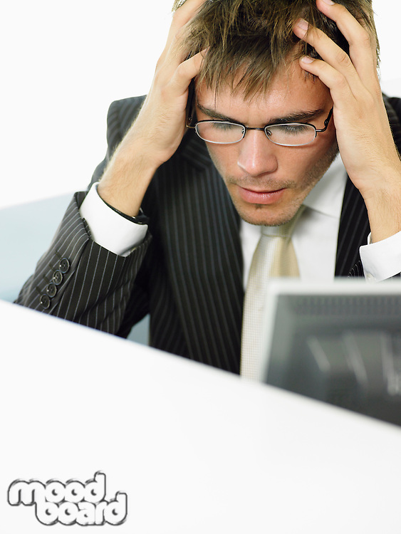 Stressed Businessman sitting at desk by computer