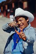 A Tarahumara Indian boy aiming a slingshot at South Orient Express passengers at Divisadero.