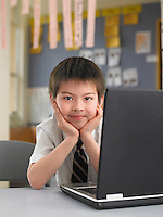 Elementary schoolboy sitting by laptop in classroom