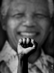 Dec. 12, 2013 - Pretoria, South Africa - A man raises a fist in support of Mandela, in front of a portrait of him. South Africans grieve loss of their leader, Nelson Mandela.<br />  (Credit Image: © Magnus Wennman/Aftonbladet/IBL/ZUMAPRESS.com)