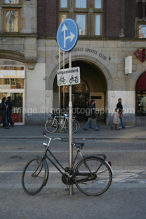Black Bicycle locked to signpost in Amsterdam<br />