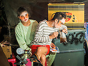 18 JANUARY 2015 - BANGKOK, THAILAND:  Performers with the Sai Yong Hong Opera Troupe relax back stage before a performance at the Chaomae Thapthim Shrine, a Chinese shrine in a working class neighborhood of Bangkok near the Chulalongkorn University campus. The troupe's nine night performance at the shrine is an annual tradition and is the start of the Lunar New Year celebrations in the neighborhood. The performance is the shrine's way of thanking the Gods for making the year that is ending a successful one. Lunar New Year, also called Chinese New Year, is officially February 19 this year. Teochew opera is a form of Chinese opera that is popular in Thailand and Malaysia.             PHOTO BY JACK KURTZ