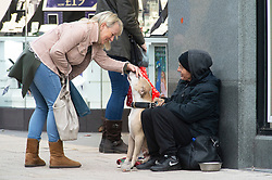 © Licensed to London News Pictures. 18/12/2018. Bromley, UK. A shoppers says hello to a homeless person and their dog. With one week to go before Christmas day, Bromley high street in South East London is very busy this afternoon with shoppers carrying bags full of gifts rather than shop online.Photo credit: Grant Falvey/LNP
