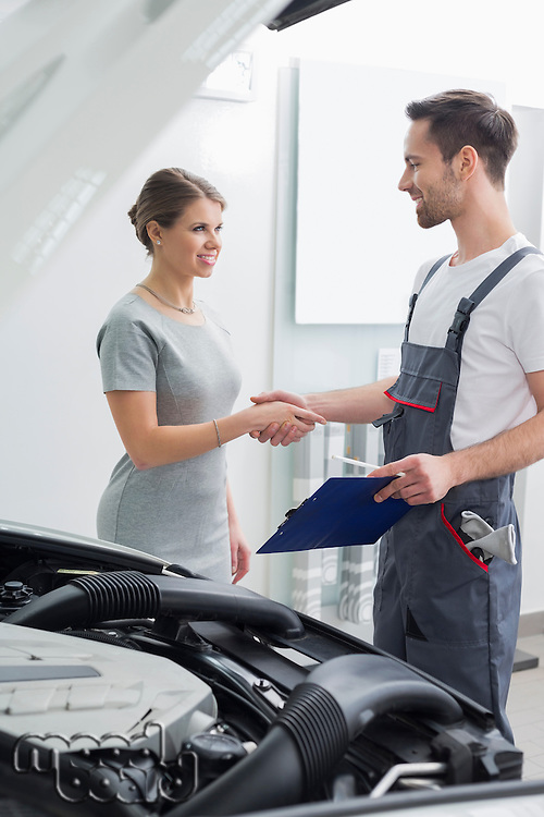 Young repair worker shaking hands with customer in car workshop