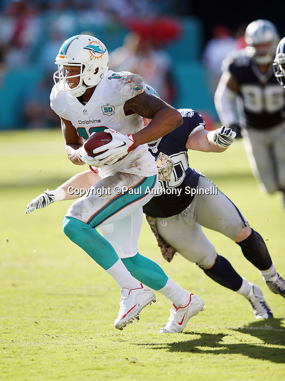 Miami Dolphins wide receiver Rishard Matthews (18) catches a third quarter pass for a first down as he tries to avoid a tackle attempt by Dallas Cowboys outside linebacker Sean Lee (50) during the 2015 week 11 regular season NFL football game against the Dallas Cowboys on Sunday, Nov. 22, 2015 in Miami Gardens, Fla. The Cowboys won the game 24-14. (©Paul Anthony Spinelli)