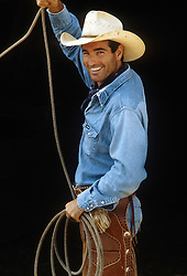 sexy cowboy in chaps holding a rope and smiling