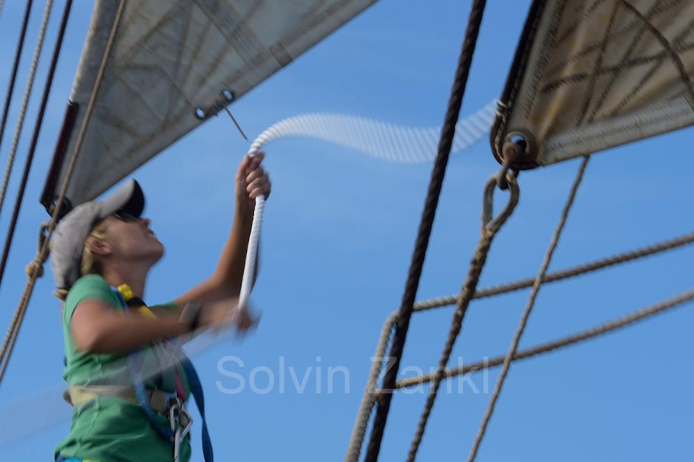 Corwith Cramer is a 134-foot steel brigantine built as a research vessel for operation under sail. Sargasso Sea, Bermuda | 2nd Mate Jill Hughes setzt das Segel auf dem Forschungssegler Corwith Cramer. Der Forschungssegler Corwith Cramer durchquert im April 2014 die Sargasso See von Puerto Rico kommend bis zu den Bermuda Inseln.