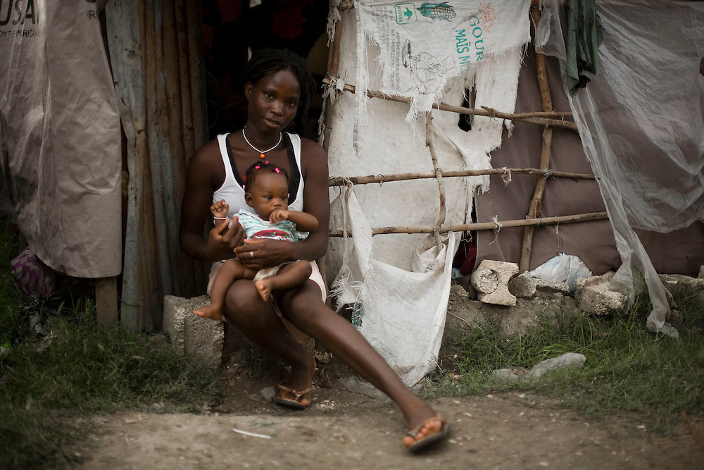 """Gracieuse Jean, and her daughter Daphene Aristène sit in the doorway of their shelter. Daphene Aristène, 6 months, was born in Santo, on the outskirts of Port-Au-Prince during the earthquake on January 12th. .Her mother, Gracieuse Jean, went into labor at 4 PM on the 12th. She ran outside when her house started shaking and while her house collapsed completely, she gave birth to Aristène at 6 PM in the street. Gracieuse also has two boys, aged 4 and 5. Her husband has been out of work since the earthquake. The whole family has been staying in a shelter made from tarps since the earthquake. Daphene Aristène's nickname is """"Goudou Goudou"""" which is a Haitian Creole slang term for earthquake."""