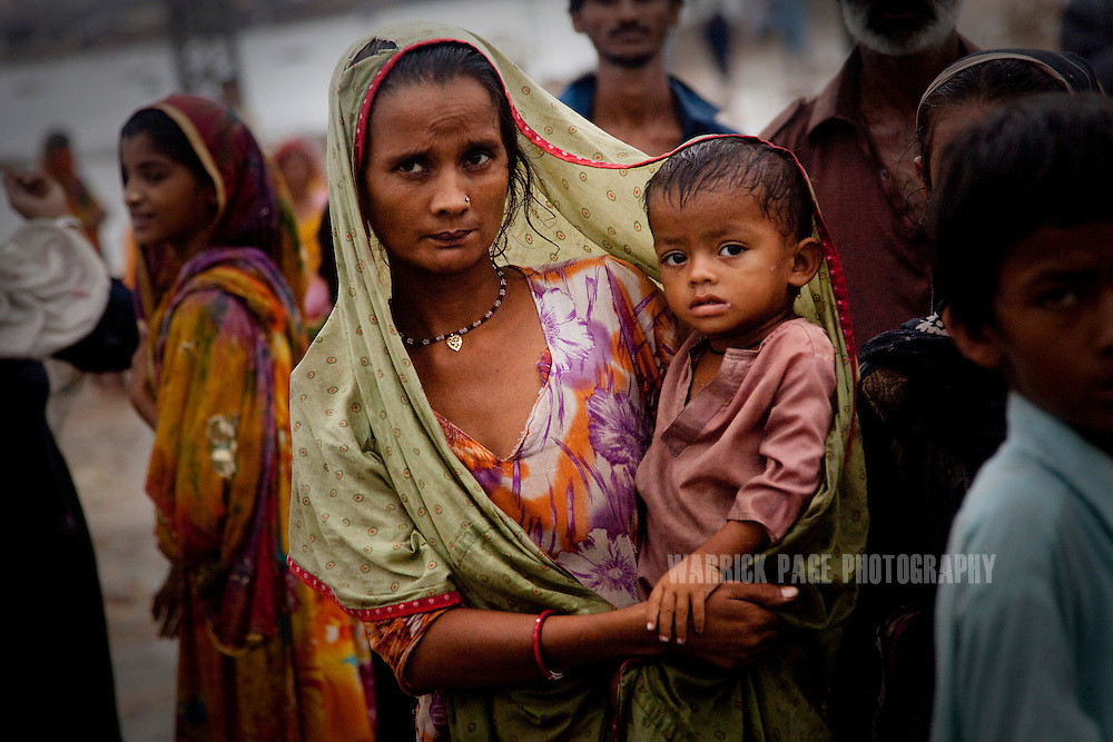 A woman holds a baby, as locals block the road in protest of the lack of government help after they were forced to evacuate their homes due to rising floodwaters, on 13 September, 2011, in Hyderabad, Pakistan. More than 17% of children in the flood areas are severely acutely malnourished and 67% of livestock has been destroyed after torrential monsoon rains, reminiscent of the 2010 floods that devastated Pakistan, have reportedly already killed over 200 people, left 300,000 homeless and affected over 7 million. (Photo by Warrick Page)