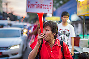 30 NOVEMBER 2013 - BANGKOK, THAILAND:  Pro-government Red Shirts walk down a street in Bangkok Saturday. Political faultlines in Bangkok, the Thai capital, hardened Saturday. Antigovernment factions repeated promises to strike at the heart of Bangkok Sunday and bring down the government while thousands of Red Shirts, who support the government, have come to Bangkok from their base in rural Thailand to defend the government. Prime Minister Yingluck Shinawatra has appealed for calm, but her opponents have rejected all requests for negotiations saying the only acceptable outcome is the eradication of the government.       PHOTO BY JACK KURTZ