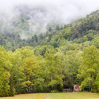 John Oliver Cabin, constructed circa 1822, sits below a blanket of fog and lush spring color in Cades Cove, Great Smoky Mountains National Park, Tennessee.