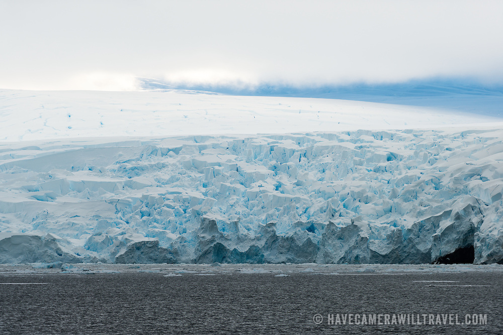 """Rugged cliffs of ice from glaciers lining the coastline of the Lemaire Channel on the western side of the Antarctic Peninsula. The Lemaire Channel is sometimes referred to as """"Kodak Gap"""" in a nod to its famously scenic views."""