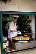 A chef cooks fried dumplings at a restaurant in the French Concession Shanghai, China