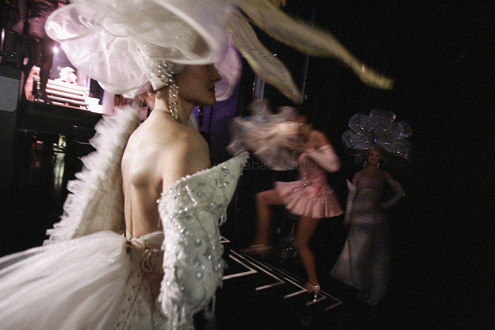 """Dancers prepare before a show 30 November 2006 at the Lido in Paris. The famous French cabaret on the Champs-Elysees will celebrate its 60th anniversary until July 2007. 500,000 spectators a year enjoy the glamorous show performed by 60 strictly selected dancers - including 25 topless """"bluebell girls"""" -, whereas, in the wings, 400 stage technicians, mechanics and craftsmen help to make the legend comes true...AFP PHOTO OLIVIER LABAN-MATTEI"""