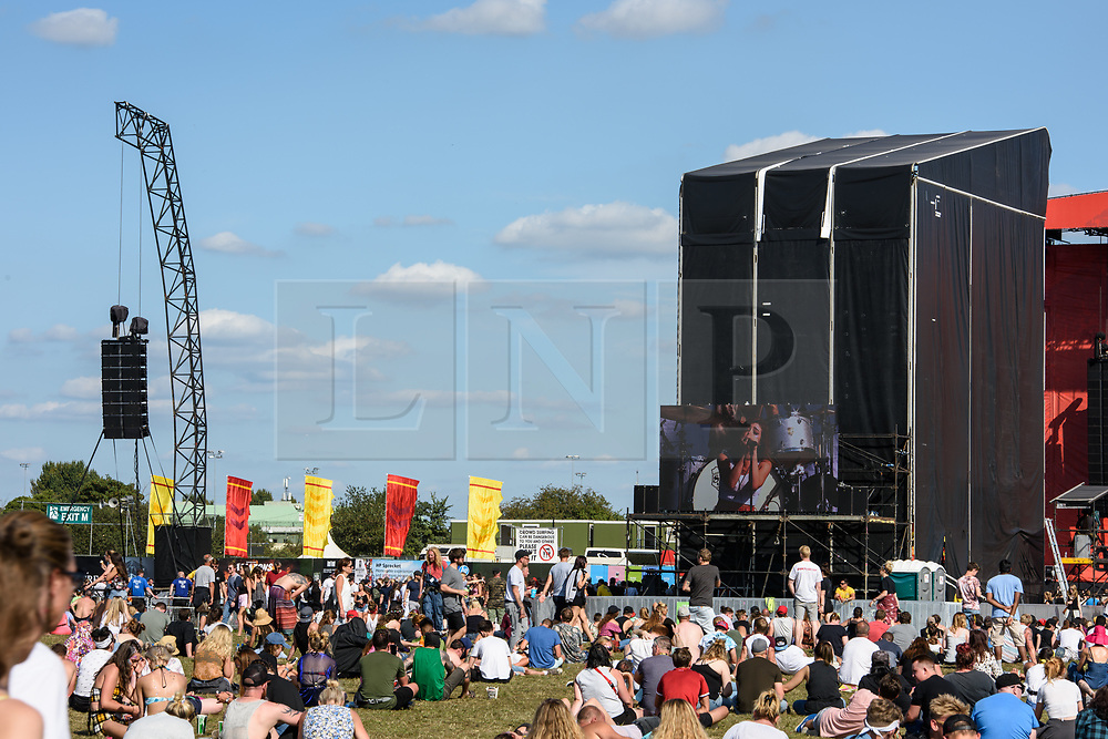 © Licensed to London News Pictures. 27/08/2017. Reading Festival 2017, Reading, UK. Pictured festival crowd and atmosphere enjoying the sunny weather on the last day of the festival. Further information, the left hand speaker tower was used by a daredevil festival goer to climb up during Eminem's performance on Saturday night, causing onsite security staff and the Royal Berkshire Fire and Rescue Service to attend and help the reveller down.  Photo credit: Andy Sturmey/LNP