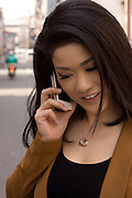 Young Japanese woman using her mobile phone in the city.