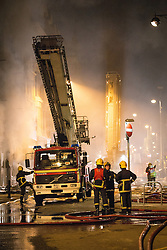© Licensed to London News Pictures . 13/07/2013 . Manchester , UK . Fire crews working at the scene . A fire fighter is dead and two 15 year old girls are under arrest on suspicion of manslaughter after a blaze in Manchester yesterday (Saturday 13th July) . More than 60 fire fighters tackled a blaze at Paul's Hair World on Oldham Street in Manchester City Centre late in to the night (Saturday 13th July 2013) . Twelve crews from four stations were deployed . Several streets in a block in the city centre are sealed off . Photo credit : Joel Goodman/LNP