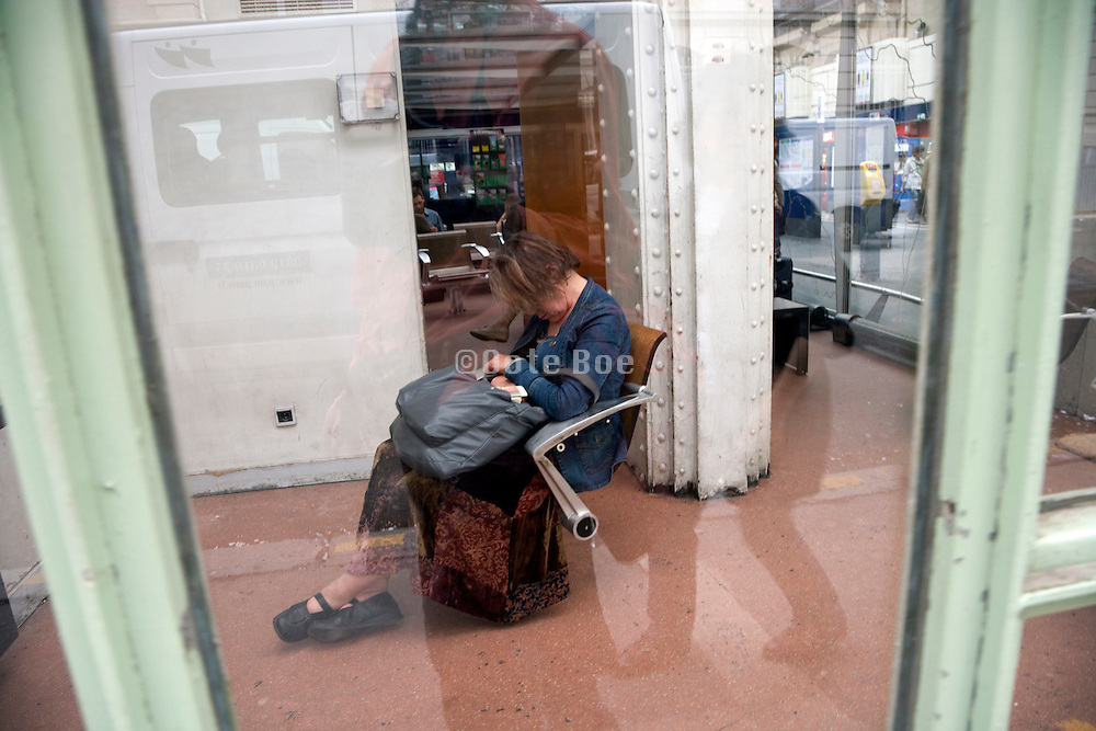 tired elderly female traveler sitting in a chair at a train station