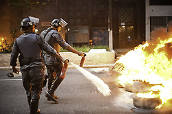 June 30, 2017 - Sao Paolo, Brazil - Riot police clash attempt to extinguish fires in the street during protests against President Michel Temer's proposed economic reforms in Sao Paulo. (Credit Image: © Anderson Barbosa/Fotoarena via ZUMA Press)