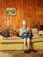 Senior woman sitting on sofa knitting (portrait)