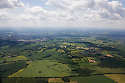 Cumulus clouds float over wheat fields are seen from a plane descending towards Luton airport, London.