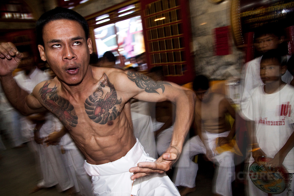 A devotee enters a trance and runs towards the altar during the Phuket Vegetarian Festival, Phuket, Thailand.