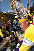 Festival supporters, wearing yellow, drag a large pine tree truck down a hill during the Onbashira matsuri which takes place every seven years in the town of Suwa, Nagano. Japan. April 10th 2010