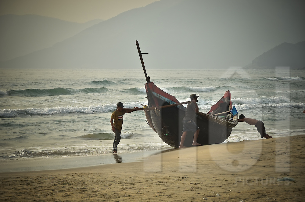 Fishermen come back after fishing and push their boat up on the beach in Lang Co, Centre Vietnam,Asia