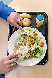 Man eating lunch from trays in the work canteen,