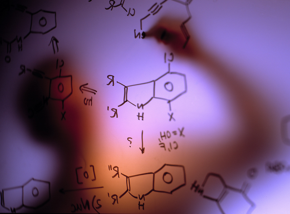 Scientist making chemical notation on frosted glass in lab