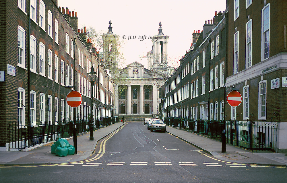 """Perspective view down Lord North street (a one way street) toward restored 18thc church of St. John the Evangelist, Smith Square, London.  The church is now a concert venue.  The street is empty except for a few parked cars and a green trash bag awaiting pick up.  Two """"do not enter"""" red traffic signs, one on each corner."""
