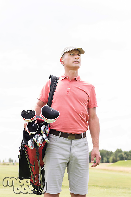 Thoughtful middle-aged man looking away while carrying golf bag against clear sky