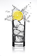 Lemon wedge being dropped into yellow liquid in a tall glass creating a perfect splash.