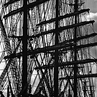 Near-silhouette of large square-rigged ship's masts and rigging.