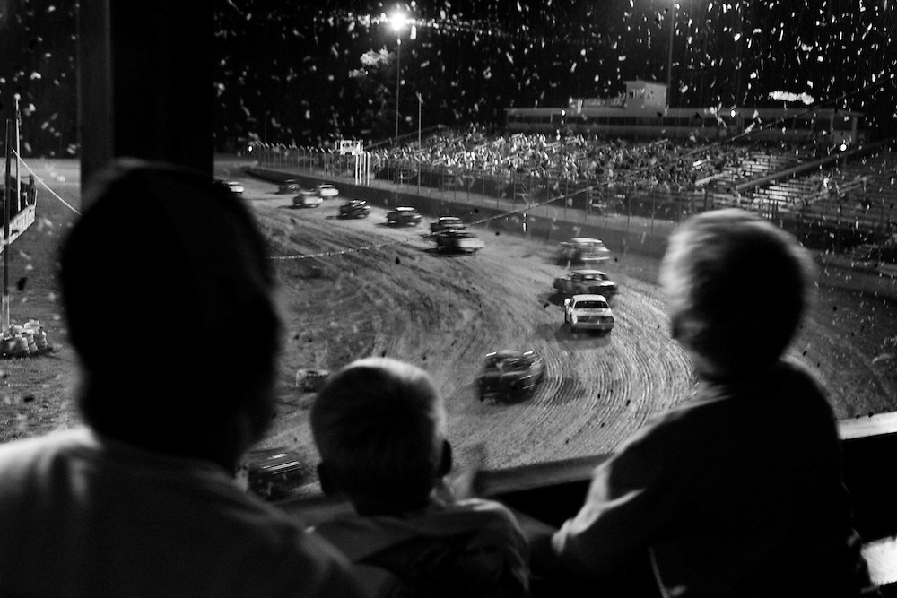 Scott Morgan/The Hawk Eye.from left: Colton Fraise, 13, Evan Williams, 8, and Breck Williams, 10, all of Burlington, watch the races from the box seats in turn 4 through mud covered glass...Saturday July 8, 2006 at the 34 Raceway in Middletown, Iowa.