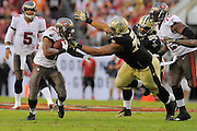 Tampa Bay Buccaneers running back Doug Martin (22) is tackled by New Orleans Saints defensive tackle Akiem Hicks (76) during an NFL game at Raymond James Stadium on Sept. 15, 2013 in Tampa, Florida. <br /> &copy;2013 Scott A. Miller