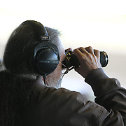 A racing enthusiast watches the race through his binoculars at Belmont Park during the Jockey Club Gold Cup Day, Belmont Park, New York. USA. 28th September 2013. Photo Tim Clayton