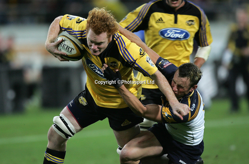 Hurricane's Paul Tito gets tackled by the Brumbies Matt Henjak during the Hurricane's 49-37 win over the Brumbies in their Super 12 match at the Westpac Trust Stadium in Wellington New Zealand on Saturday night. 30 April 2005 Photo: Marty Melville/Photosport