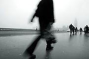 Commuters with Big Ben and parliament in the background on a misty fog bound westminster bridge London mono