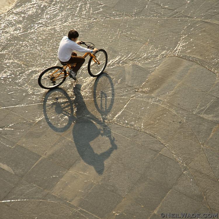 A boy rides his bicycle through some water in Bitan, Taipei, Taiwan.