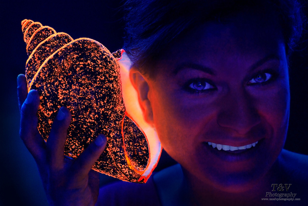 A woman smiles as she listens to a glowing sea shell.Black light
