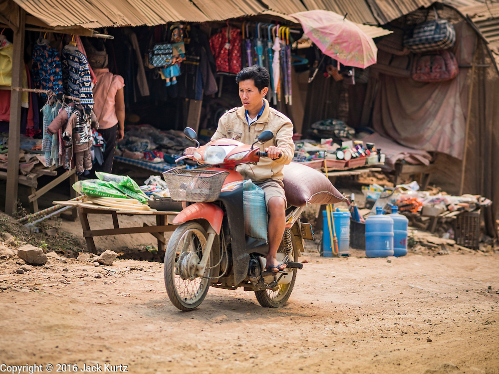 11 MARCH 2016 - LUANG PRABANG, LAOS: A man rides his motorcycle through the community of Chomphet, across the Mekong River from Luang Prabang. Laos is one of the poorest countries in Southeast Asia. Tourism and hydroelectric dams along the rivers that run through the country are driving the legal economy.       PHOTO BY JACK KURTZ