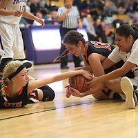 Aztec Tigers Reigan Weaver (32), Adrianna Sanders (12) and Miyamura Patriot Destiny Lee (32) all try to gain possession of the ball during Saturday;s game at Miyamura.