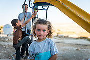 A Palestinian girl stands in front of a slide in Susiya.