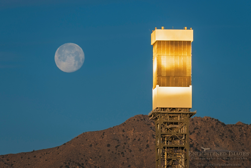Sunrise light reflected on Solar Array Energy Collector in front of setting full moon, Ivanpah Solar Electric Generating System, Nipton, California
